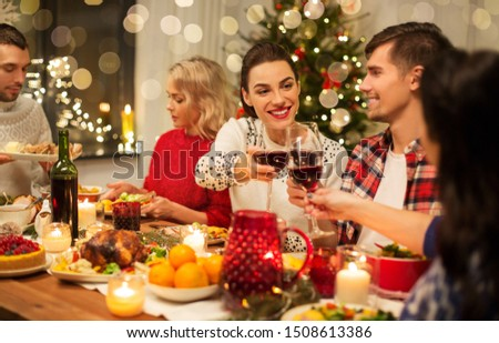 holidays and celebration concept - happy friends having christmas dinner at home, drinking red wine and clinking glasses #1508613386