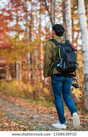 A man with camera & camera bag is walking into natural walk way surounded by autumn color quaking tree. Concept of explore the nature #1508638910