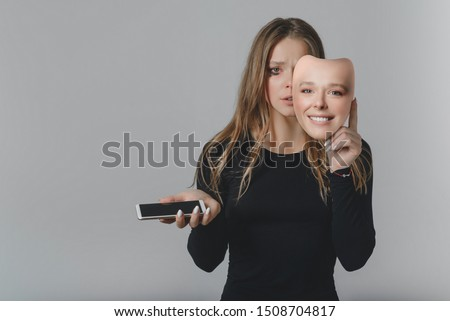 Portrait of a sad girl with a smartphone in one hand and a smiling mask in the other hand, with which she covers her face, as a symbol of the inconsistency of the image of a person in social networks