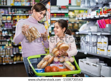 Young cheerful positive woman customer with girl looking for tasty bread in supermarket #1508730563