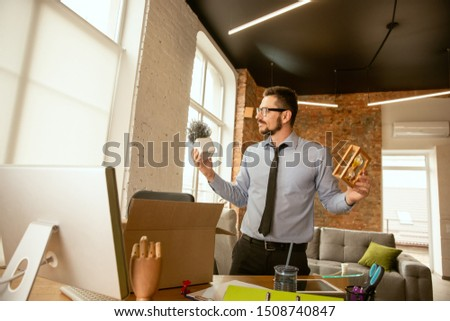 Beginning. A young businessman moving in the office, getting new work place. Young male office worker equips new cabinet after promotion. Looks happy. Business, lifestyle, new life concept. Unpacking. #1508740847