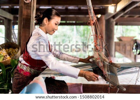 side view of Asian woman weaving silk sari on loom. female works on cotton or silk weaving with traditional hand weaving loom. Asian traditional culture. concept of life, people and Small business #1508802014