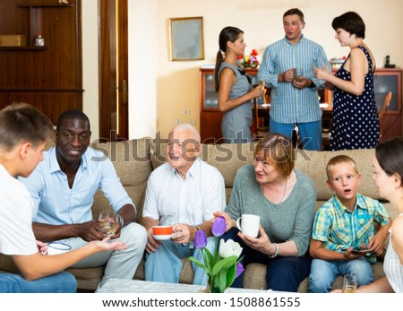 Portrait of big multigenerational family  chatting on sofa at home  #1508861555