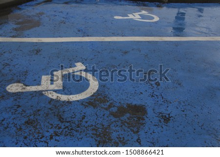 heavy rain covering blue icon traditional disabled zone painted sign weathered and damaged #1508866421
