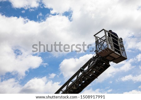 Firefighters rescue people in high building to escape by extended ladder crane of fire truck on blue sky, fire drill #1508917991