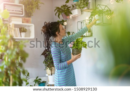 Young woman taking care of her potted plants at home  #1508929130