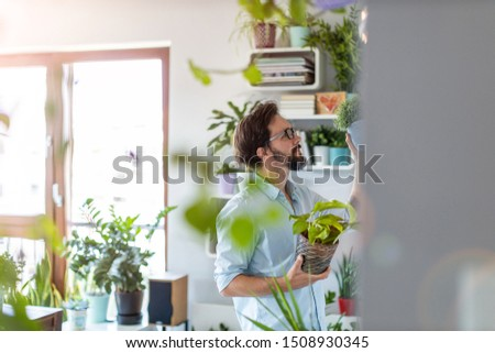 Man taking care of her potted plants at home  #1508930345