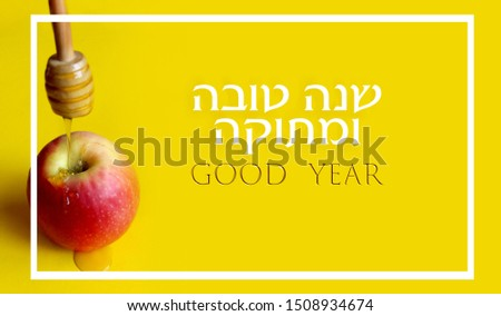 This is a picture of a single apple from above and honey on a yellow background. This is a symbol of a Jewish holiday with Hebrew text that says Happy New Year and a text in English