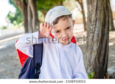 Arabic muslim boy with his backpack on his back going to school #1508950055