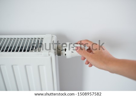 Woman Hand Adjusting The Knob Of Heating Radiator. The valve from the radiator - Heating. Hand adjusting thermostat valve of heating radiator in a room. Copy space. #1508957582
