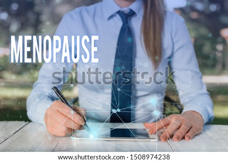 Conceptual hand writing showing Menopause. Business photo showcasing Period of peranalysisent cessation or end of menstruation cycle Female human wear formal work suit presenting smart device. #1508974238