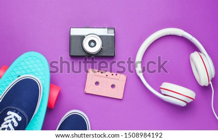 Hipster fashion look. Skateboard, sneakers, audio cassette, retro camera, headphones on purple color background. 80s. Top view. Flat lay Royalty-Free Stock Photo #1508984192
