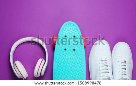 Hipster outfit. Skateboard with headphones and sneakers on purple background. Creative fashion minimalism. Trendy old fashionable style. Minimal summer fun. Music concept #1508998478
