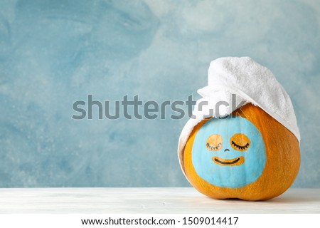 Pumpkin with facial mask and towel on wooden background, copy space #1509014417