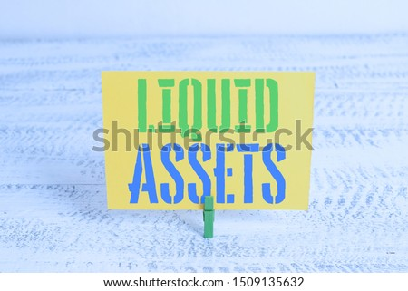 Text sign showing Liquid Assets. Conceptual photo Cash and Bank Balances Market Liquidity Deferred Stock Green clothespin white wood background colored paper reminder office supply. #1509135632