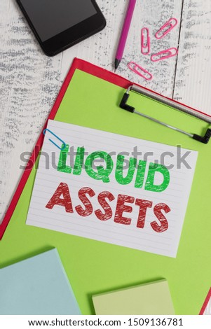 Word writing text Liquid Assets. Business concept for Cash and Bank Balances Market Liquidity Deferred Stock Clipboard sheet pencil smartphone note clips notepads wooden background. #1509136781