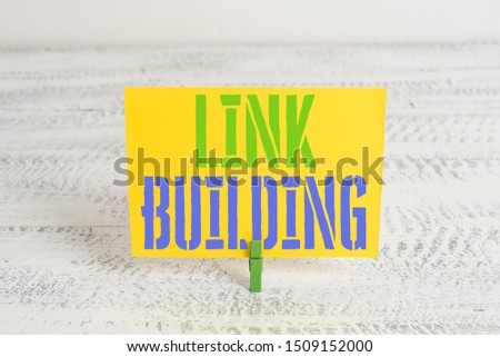 Text sign showing Link Building. Conceptual photo SEO Term Exchange Links Acquire Hyperlinks Indexed Green clothespin white wood background colored paper reminder office supply. #1509152000