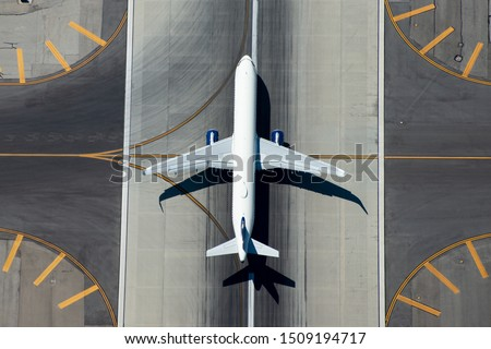 Aerial view of narrow body aircraft departing airport runway.