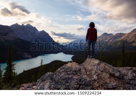 Adventurous girl standing on the edge of a cliff overlooking the beautiful Canadian Rockies and Peyto Lake during a vibrant summer sunset. Taken in Banff National Park, Alberta, Canada. #1509224234
