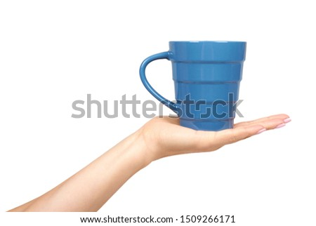 Hand with blue ceramic cup, mug for coffee and tea, kitchen pottery. Isolated on white background. #1509266171
