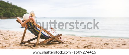 Summer beach holiday concept. Young asian woman relaxing on beach chair arm up her hand with floppy hat. White sand cler sky background banner with copy space. Pattaya, Thailand #1509274415
