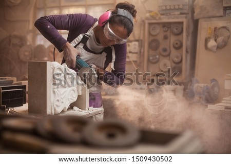 Female stonemason cutting a piece of white marble in a workshop, craftswoman grinding a sculpture with angle grinder, dust and debris flying, women doing hard work concept, stonemasonry and stonecraft #1509430502
