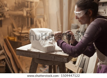 Female sculptor at work in a workshop, using hammer and chisel to sculpt a piece of white marble stone, debris and particles flying around, stonemasonry and stonecraft, copy space #1509447122