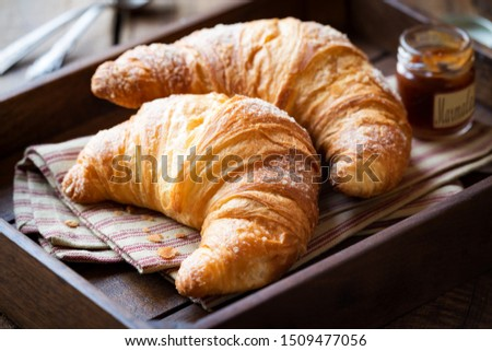 Good morning concept - Freshly baked croissants on a tray with a small jar of jam for breakfast #1509477056