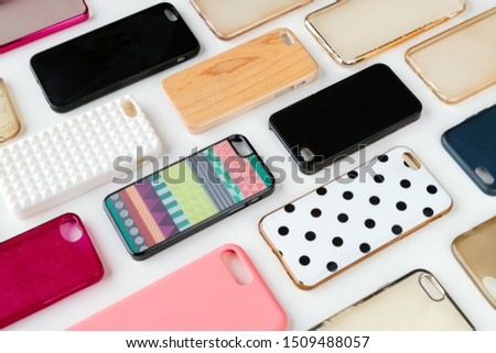 Pile of multicolored plastic back covers for mobile phone. Choice of smart phone protector accessories background. A lot of silicone phone backs or skins next to each other #1509488057