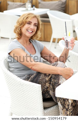 Portrait of a woman with happy expression holding glass of water at restaurant #150954179