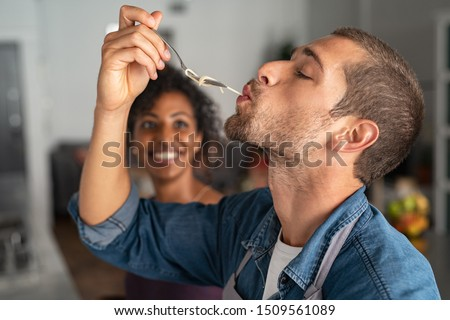 Man tasting spaghetti pasta while smiling woman look at him. Closeup face of young man tasting meal while cooking at home. Handsome guy eating noodles with fork in kitchen and feel his recipe. #1509561089