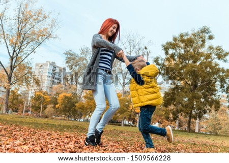 Low angle view f mother and son having fun while holding hands and spinning in autumn day. #1509566228