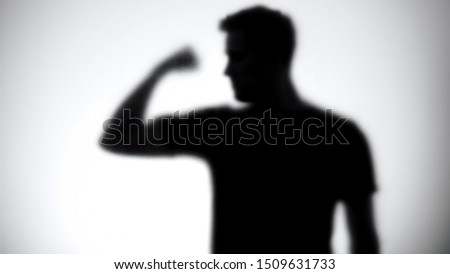 Silhouette of confident man showing biceps, bodybuilding and fitness, close-up #1509631733