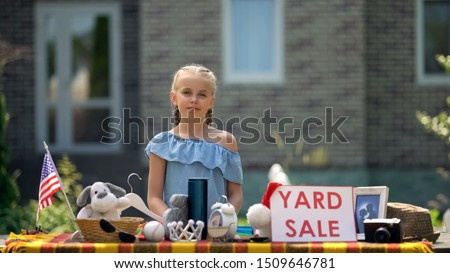 Young business lady selling old toys on yard sale, earning extra pocket money