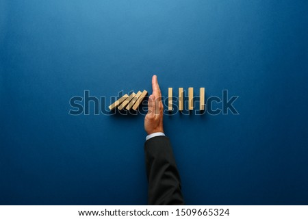 Top view  of businessman hand stopping falling dominos in a business crisis management conceptual image. #1509665324