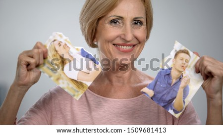 Satisfied mother smiling with torn couple photo, interference in relationship #1509681413