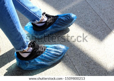 blue disposable shoe covers are worn on the upper shoes #1509800213