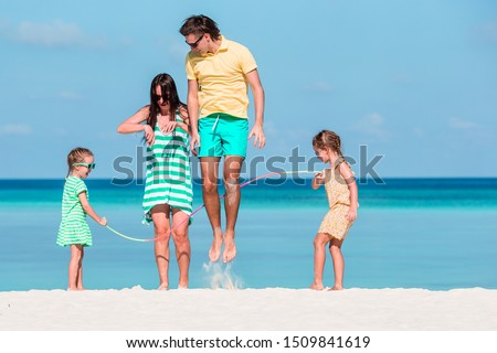 Parents play with kids on the beach #1509841619