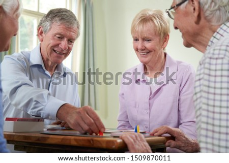 Group Of Retired Friends Playing Board Game At Social Club  #1509870011