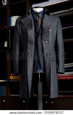 Elegance bespoke winter-coat with suit, brown tie and navy blue shirt on a mannequin. Men's Clothing. #1509878537