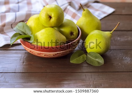 ripe green pears in a bowl on a wooden background. fresh pear closeup. background with yellow-green pears and leaves. Royalty-Free Stock Photo #1509887360