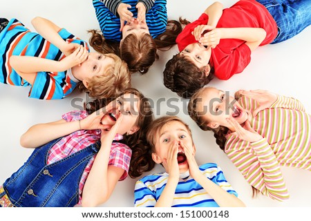 Group of cheerful children lying on a floor together. Isolated over white. #151000148