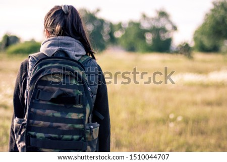 young woman walking outside in a field full of plants and carrying a backpack while enjoy the view  #1510044707