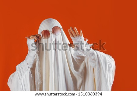 Happy Halloween. Cute funny Ghost on a bright orange background. Sheet Ghost costume, Halloween party carnival. Lovely ghost waving Hello #1510060394