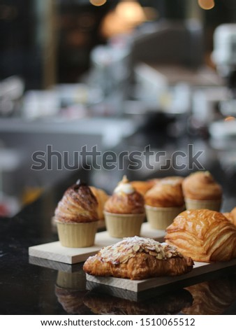 Assorted pastries in a bakery. Croissant, cronut, cruffin on a dark table. Fresh pastry on display. Cafe selling pastries. #1510065512