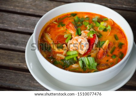 """Thai national favorite food spicy shrimp or prawn  curry call """"Tom Yum Kung"""" in white bowl on wooden table at local restaurant #1510077476"""