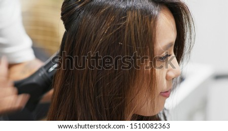 Hairdresser blow hair with dryer in the salon #1510082363
