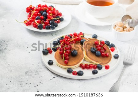Sweet pancakes with red currants and blueberries. Wholesome breakfast #1510187636
