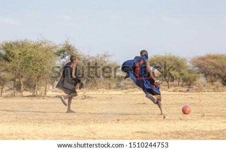 Arusha, Tanzania, 7th September 2019: maasai warriors playing football in savannah #1510244753