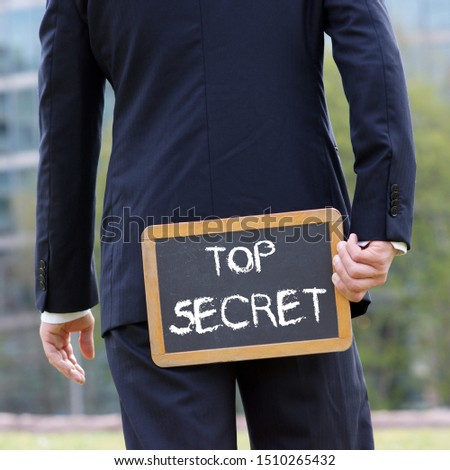 Business man holding a blackboard behind himself with the words Top Secret written with chalk #1510265432